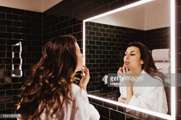 mid adult woman looking in mirror while applying lip balm - lip balm stock pictures, royalty-free photos & images
