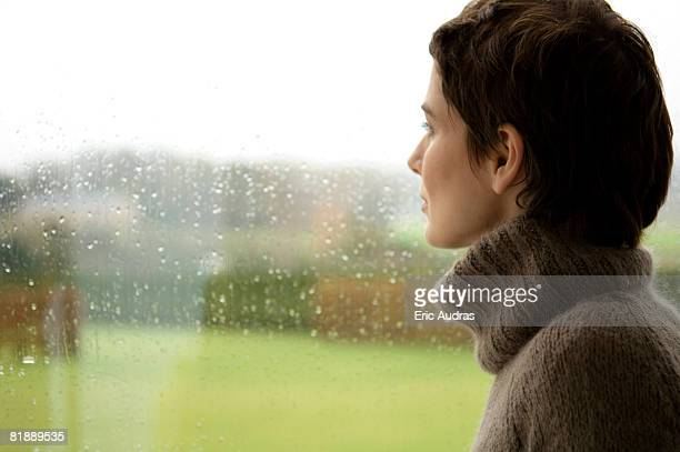 Mid adult woman looking out through a window