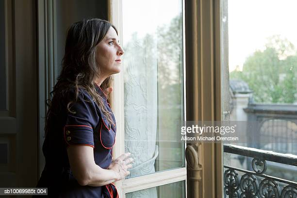 Mid adult woman looking out window of apartment