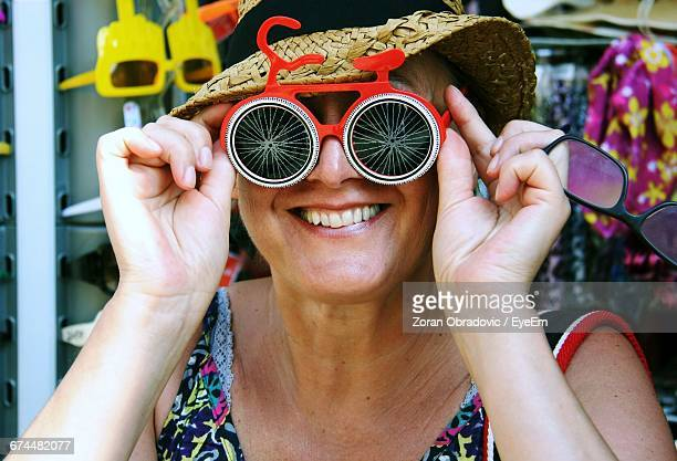 mid adult woman looking through funky sunglasses - multi colored hat stock pictures, royalty-free photos & images