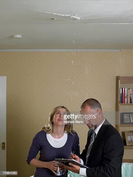 Mid adult woman looking up at water dripping from ceiling, mature man writing on clipboard