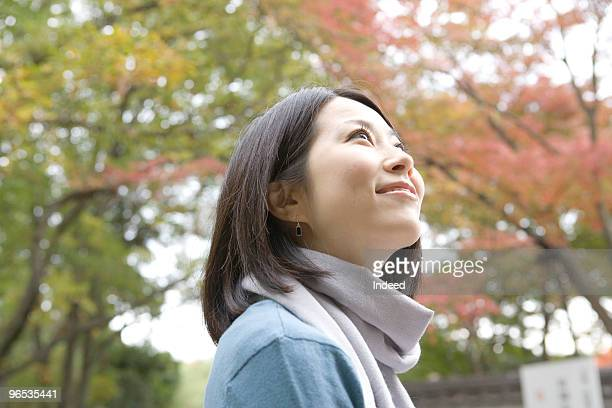 Mid adult woman looking up in forest, smiling