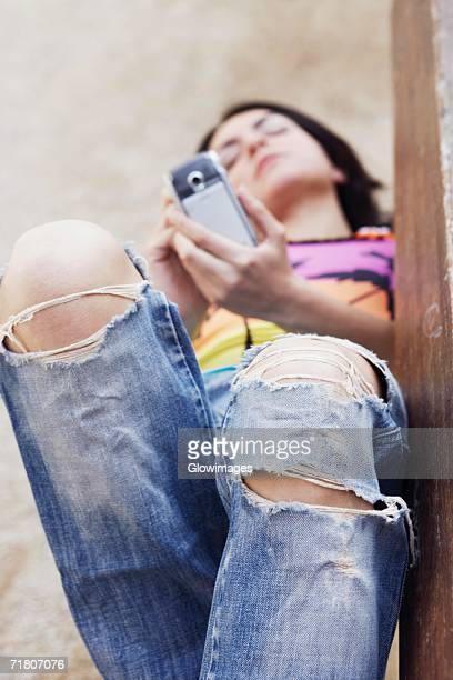 Mid adult woman lying on a bench and using a mobile phone