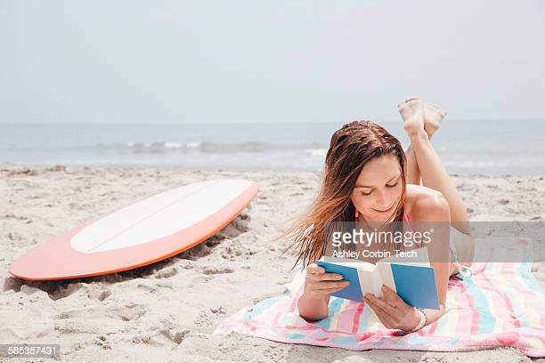 Mid adult woman lying on beach, reading book