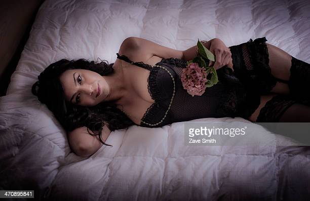 mid adult woman lying on bed holding flower - stockings and suspenders - fotografias e filmes do acervo