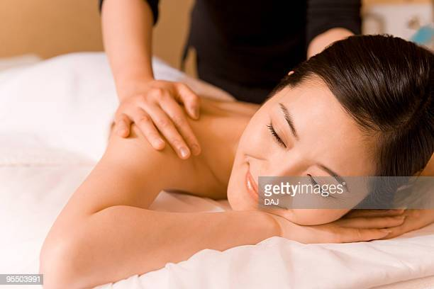 mid adult woman lying on bed in beauty salon, taking massage - massage rooms photos et images de collection