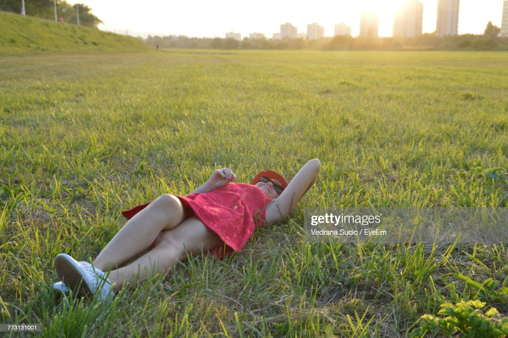 Mid Adult Woman Lying On Grassy Field During Sunset : Photo
