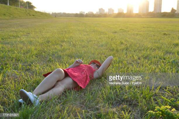Mid Adult Woman Lying On Grassy Field During Sunset