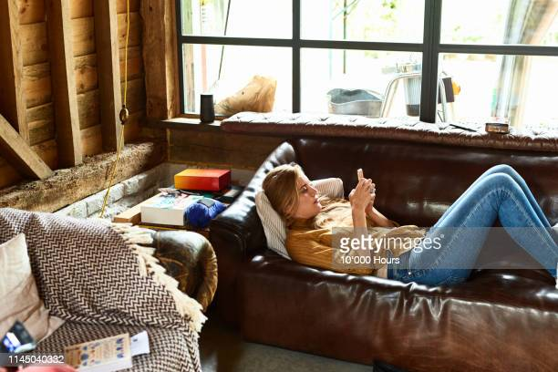 mid adult woman lying on sofa using smartphone - candid forum stock pictures, royalty-free photos & images