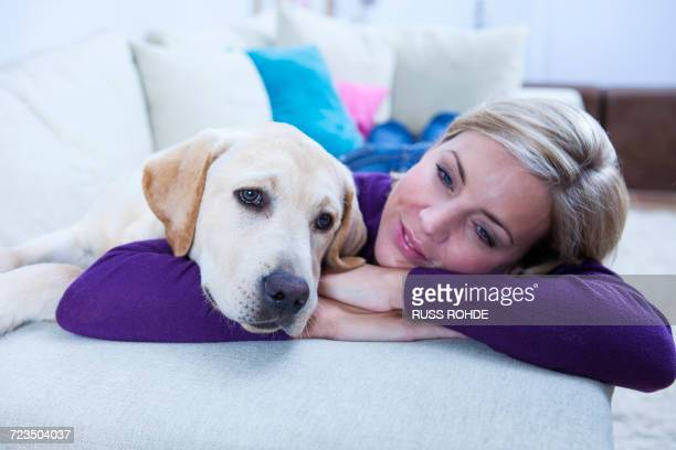 Mid adult woman lying on sofa with her labrador dog