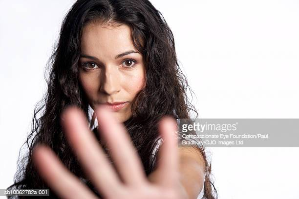 "mid adult woman making stop gesture, portrait - ""compassionate eye"" stock-fotos und bilder"