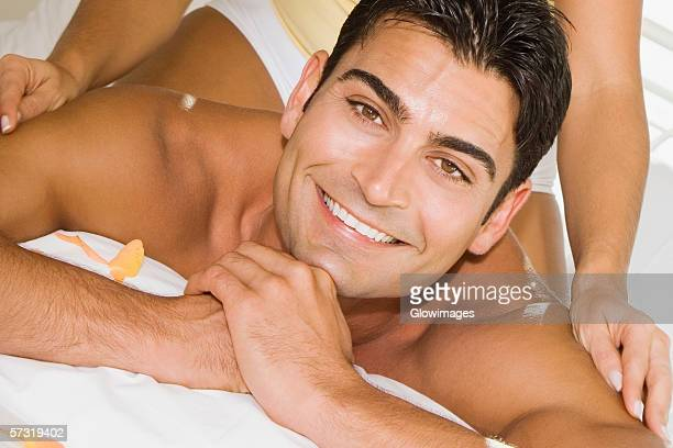 Mid adult woman massaging a mid adult man's shoulders on the bed