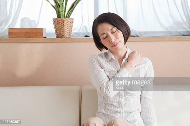 Mid adult woman massaging shoulder