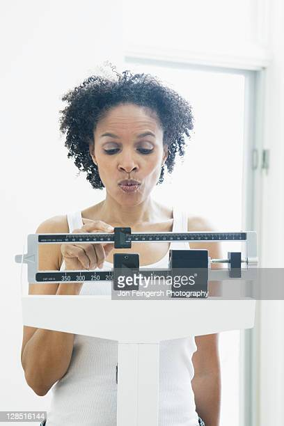 Mid adult woman measuring her weight on a weighing scale