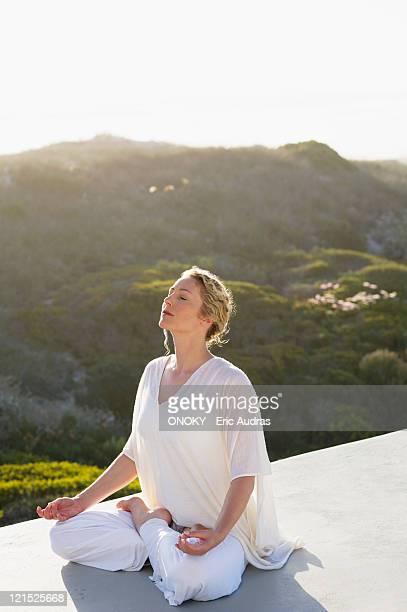 mid adult woman meditating - onoky stock-fotos und bilder