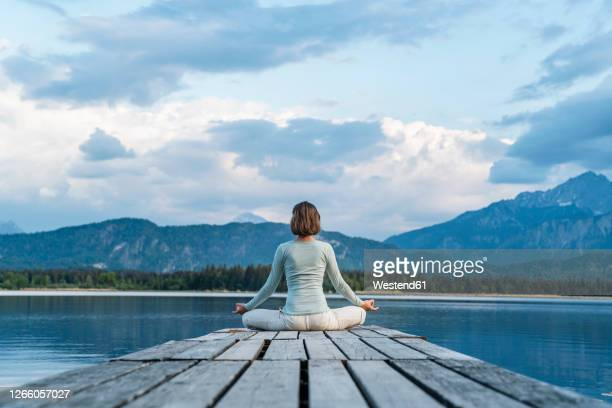 mid adult woman meditating while sitting on jetty over lake against cloudy sky - jetty stock pictures, royalty-free photos & images