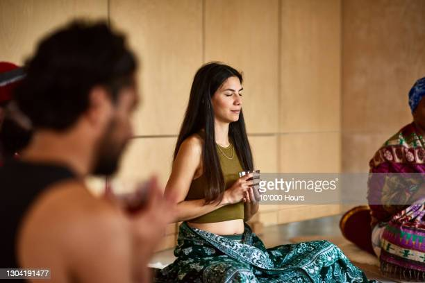 mid adult woman meditating with glass of tea in yoga studio - drink stock pictures, royalty-free photos & images
