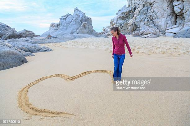 mid adult woman on beach, drawing heart shape with feet - shuffling stock photos and pictures