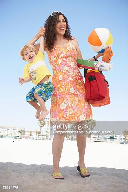 Mid adult woman on beach, holding beach gear and son (2-3) in air
