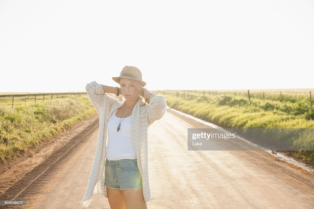 Mid adult woman on country road, arms behind neck, looking at camera : Stock Photo