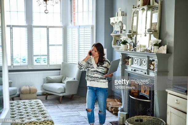 mid adult woman on phone with laptop in living room - complaining stock pictures, royalty-free photos & images