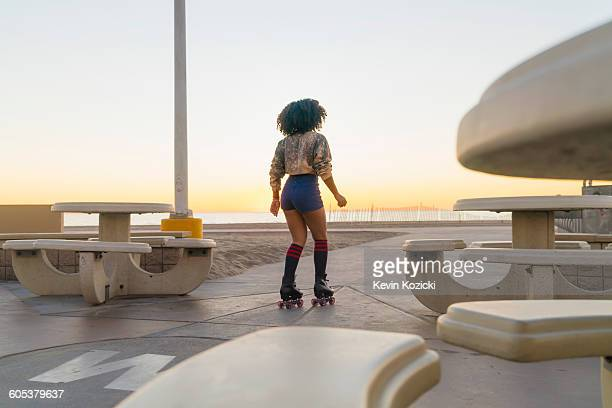 Mid adult woman on rollerskates, near beach, rear view