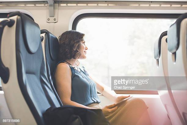 Mid adult woman on train, holding digital tablet, looking out of window