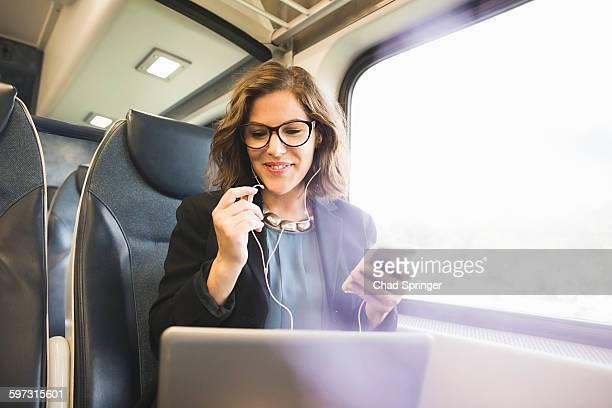 mid adult woman on train, holding smartphone, looking at laptop - 列車の車両 ストックフォトと画像