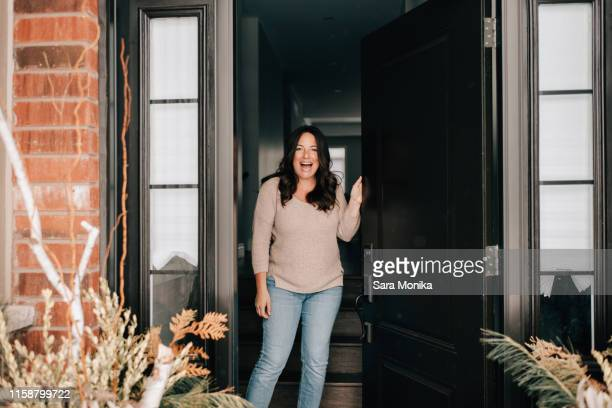 mid adult woman opening house front door, portrait - verrassing stockfoto's en -beelden