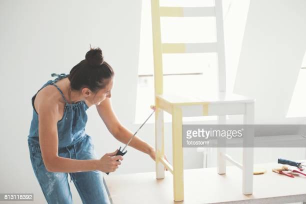 mid adult woman painting chair - mobília imagens e fotografias de stock