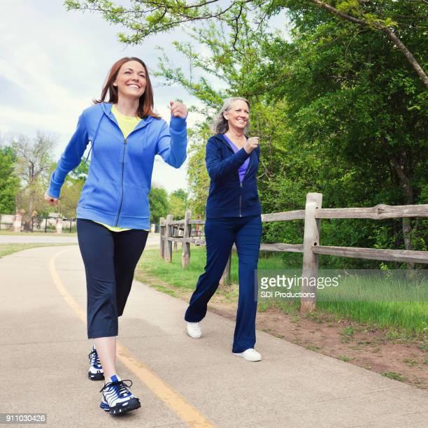 Mid volwassen vrouw passeert senior vrouw tijdens macht wandeling