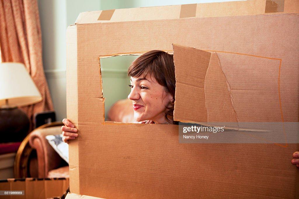 Mid adult woman peeking out of cardboard box window in living room : Stock Photo