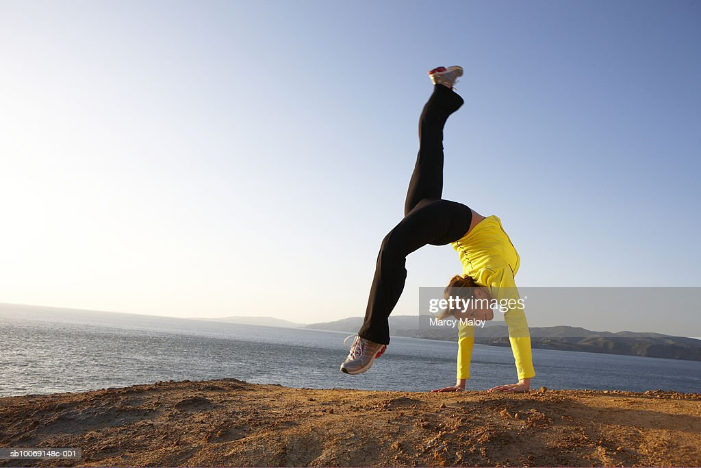 Mid adult woman performing handstand on seashore : Stockfoto