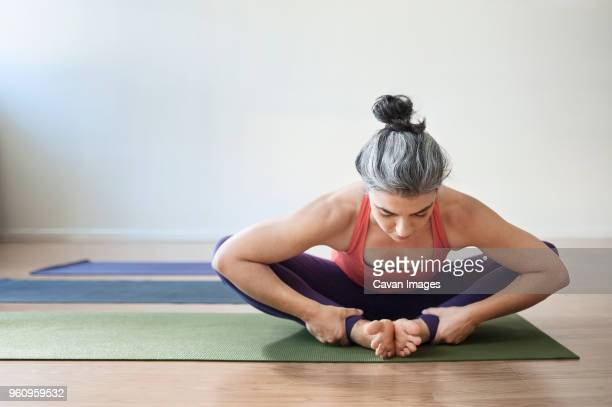 Mid adult woman performing yoga in bound angle pose at gym