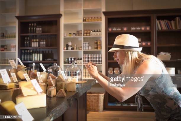 mid adult woman photographing cheeses on smartphone in organic grocery - heshphoto stock pictures, royalty-free photos & images