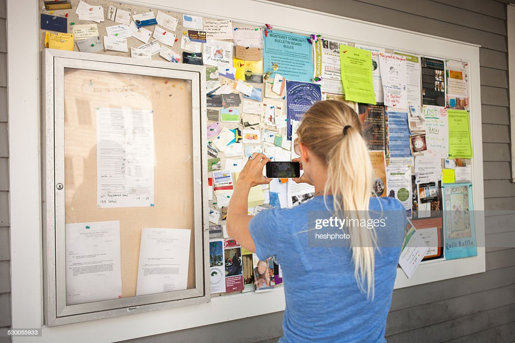 Mid adult woman photographing community notice board with smartphone : Stock Photo