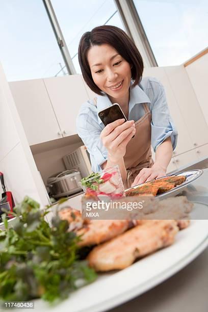 Mid adult woman photographing dishes
