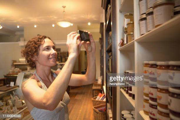 mid adult woman photographing preserves on smartphone in organic grocery - heshphoto stockfoto's en -beelden