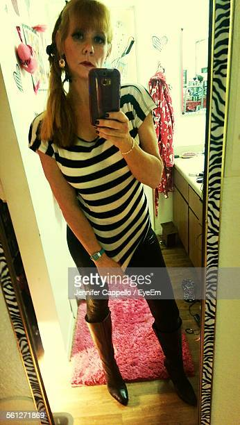 mid adult woman photographing self in mirror - taken on mobile device stock photos and pictures