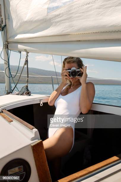 Mid adult woman photographing through camera while standing in yacht