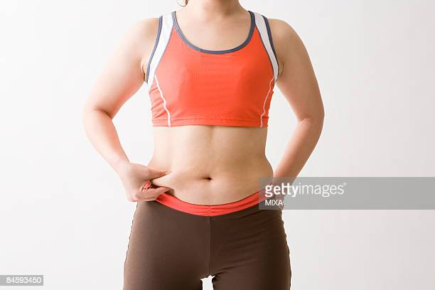 mid adult woman pinching fat on waist - metabolic syndrome stock pictures, royalty-free photos & images