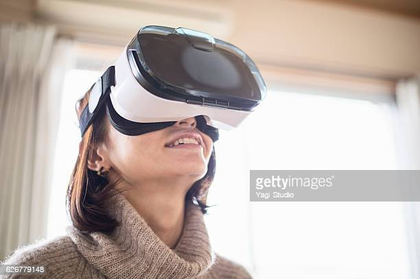 Mid adult woman playing in virtual reality glasses in bedroom