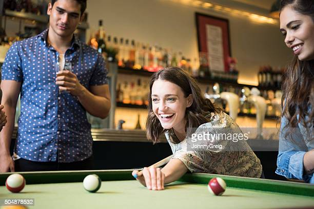 Mid adult woman playing pool in bar with friends, smiling