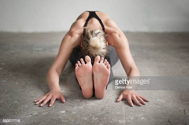mid adult woman practicing seated forward bend pose in yoga studio, munich, bavaria, germany - soles pose stock pictures, royalty-free photos & images