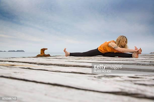 mid adult woman practicing yoga on wooden sea pier - split acrobatiek stockfoto's en -beelden