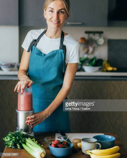 mid adult woman preparing food on table at home - mid adult stock pictures, royalty-free photos & images