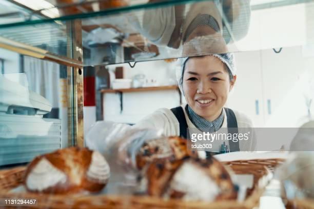 ミッドアダルト女性は、彼女の小さなビジネスベーカリーのディスプレイにパンを入れて - 郷土料理 ストックフォトと画像