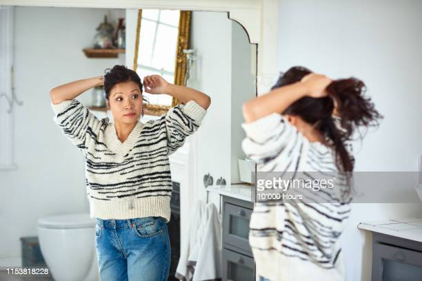 mid adult woman putting hair up and looking in mirror - haar naar achteren stockfoto's en -beelden
