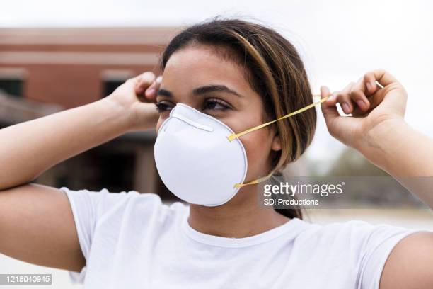 mid adult woman putting on n95 face mask - respirator mask stock pictures, royalty-free photos & images