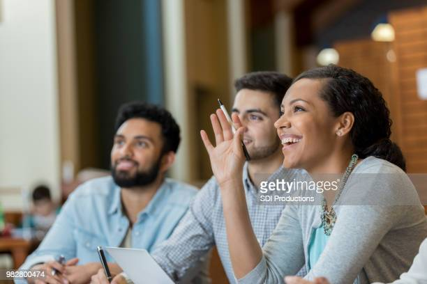 mid adult woman raises hand duirng college class - arms raised stock pictures, royalty-free photos & images